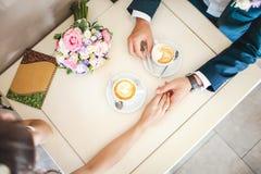 在咖啡馆的婚礼夫妇,顶视图 人握妇女的手,喝浓咖啡 新娘和新郎咖啡休息约会礼物 免版税库存图片