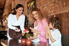 在咖啡馆的家庭 女服务员服务巧克力照顾的和儿子 免版税库存图片