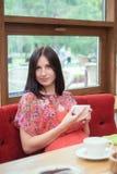 在咖啡馆的少妇饮用的茶 免版税库存图片