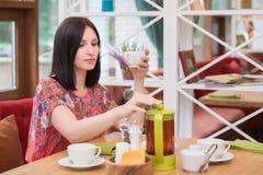 在咖啡馆的少妇饮用的茶 免版税图库摄影