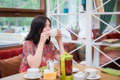 在咖啡馆的少妇饮用的茶 库存图片