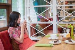 在咖啡馆的少妇饮用的茶 图库摄影