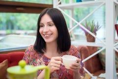 在咖啡馆的少妇饮用的茶 免版税库存照片