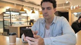 在咖啡馆的年轻人键入的消息,浏览在电话 影视素材