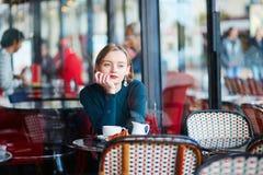 在咖啡馆的年轻端庄的妇女饮用的咖啡在巴黎,法国 免版税库存图片