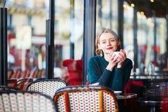 在咖啡馆的年轻端庄的妇女饮用的咖啡在巴黎,法国 免版税库存照片