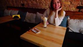 在咖啡馆的微笑的女孩选址用冰淇凌点心 股票录像