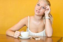 在咖啡馆的微笑的少妇饮料咖啡 免版税库存照片
