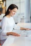 在咖啡馆的微笑的少妇读书报纸 免版税库存照片