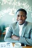 在咖啡馆的微笑的非洲商人 库存照片
