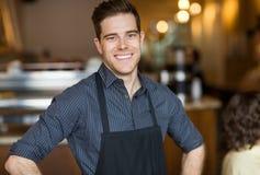 在咖啡馆的愉快的男性所有者 免版税图库摄影