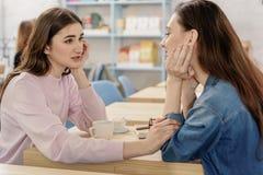 在咖啡馆的愉快的年轻女同性恋的夫妇 免版税图库摄影