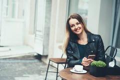 在咖啡馆的无忧无虑的时间 有坐在咖啡馆室外和键入的快的消息的微笑的可爱的少妇 图库摄影