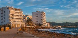 在咖啡馆的日落在伊维萨岛海滩 灿烂光辉作为太阳在St安东尼de Portmany巴利阿里群岛,西班牙进来下来 免版税库存图片