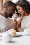 在咖啡馆的深情的微笑的非裔美国人的夫妇感人的手 免版税图库摄影