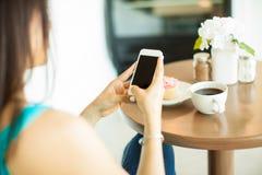 在咖啡馆的短信的和饮用的咖啡 库存照片