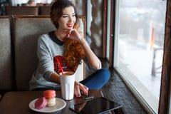 在咖啡馆的红发女孩饮用的咖啡 免版税库存照片