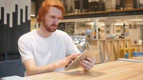 在咖啡馆的红头发人人键入的消息,浏览在片剂个人计算机 图库摄影