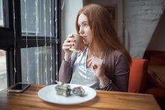 在咖啡馆的红头发人女孩饮用的茶 免版税图库摄影