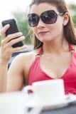 在咖啡馆的美丽的少妇移动电话Texting 免版税图库摄影