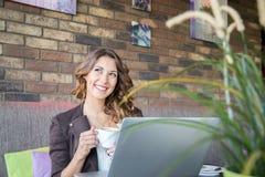 在咖啡馆的美丽的少妇饮用的咖啡 免版税库存照片