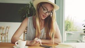 在咖啡馆的美丽的年轻人用途智能手机 免版税库存图片