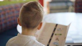 在咖啡馆的英俊的年轻男孩读书菜单 4K 股票录像