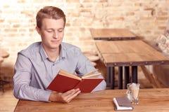 在咖啡馆的年轻英俊的人阅读书 免版税库存图片