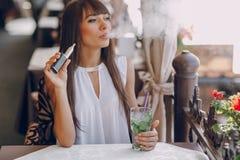 在咖啡馆的Girn与E香烟 免版税图库摄影