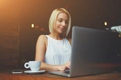 在咖啡馆酒吧的早餐期间妇女自由职业者研究便携式计算机 图库摄影