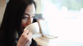 在咖啡馆饮用的热奶咖啡周道的开会的美好的性感的开会由窗口认为梦想 股票录像