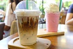 在咖啡馆,与冰块的冰冻咖啡在木背景的一个杯子 图库摄影
