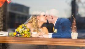 在咖啡馆,亲吻新娘的新郎的逗人喜爱的已婚夫妇 纯柔软 免版税图库摄影