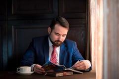 在咖啡馆读书杂志的年轻商人 免版税库存照片