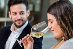 在品尝的妇女嗅到的白葡萄酒 免版税库存图片