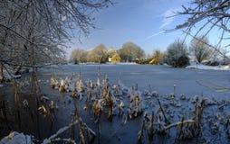 在哈特利Mauditt池塘的结冰的冬天场面圣伦纳德的教会的,南下来国立公园,汉普郡,英国 免版税图库摄影
