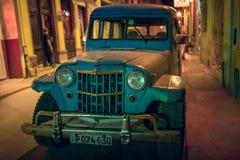 在哈瓦那夜街道的减速火箭的汽车  免版税库存照片