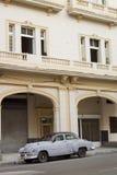 在哈瓦那大厦前面停放的浅灰色的汽车 库存照片