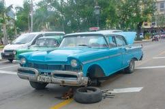 在哈瓦那街道的失败的蓝色经典美国汽车有平的轮胎的 免版税库存图片