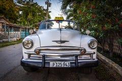 在哈瓦那,古巴附近的白色经典老朋友出租汽车 免版税库存照片