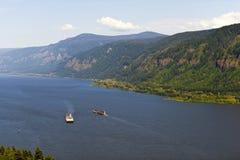 在哥伦比亚河的两艘驳船有多小山银行的 免版税库存照片