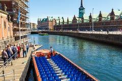 在哥本哈根渠道的旅游驳船 在背景联交所中 图库摄影