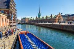 在哥本哈根渠道的旅游驳船 在背景联交所中 免版税库存图片