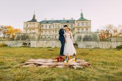 在哥特式城堡的野餐 新婚佳偶在绿色草甸花费他们的时间 库存图片
