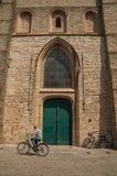 在哥特式教会的木门和骑自行车者在布鲁日 免版税库存照片
