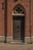 在哥特式样式的木门在日落,在布鲁日胡同  库存照片