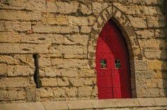 在哥特式样式的红色木门在跟特的市中心 库存照片