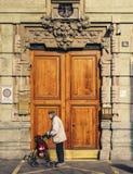在哥特式门面前面的更老的人和巨大的木门在米兰,伦巴第,意大利 库存图片