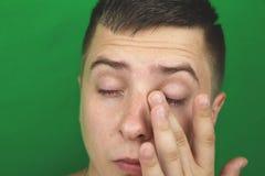 在哭泣的成人人的眼睛的泪花 绿色背景 chromakey 免版税库存照片