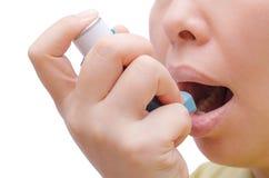 在哮喘病发作期间,妇女使用一台吸入器 库存图片